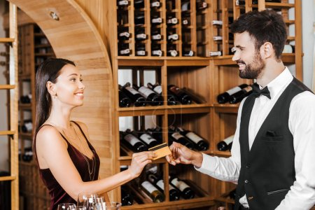 wine steward taking credit card from female customer at wine store