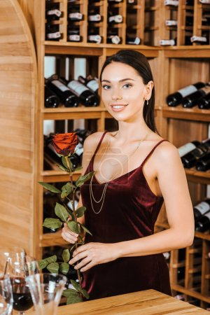beautiful woman in red dress with rose flower at wine store
