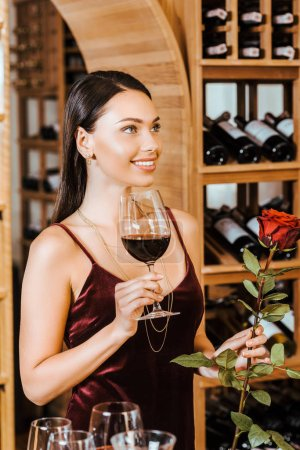beautiful woman in red dress with wine and rose looking at side at wine store