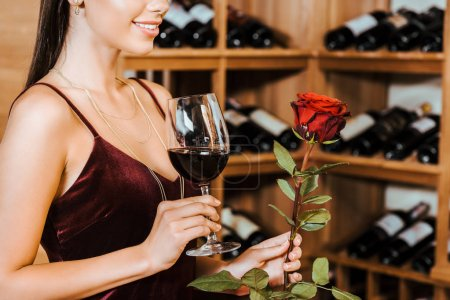cropped shot of beautiful woman in red dress with wine and rose at wine store