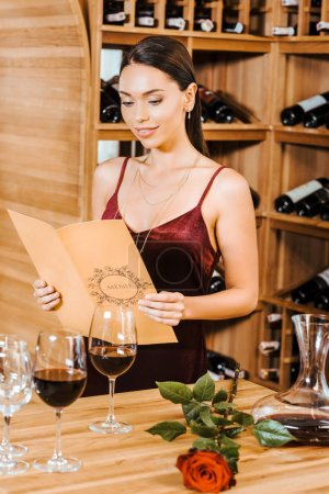 beautiful woman in red dress reading wine card at wine store