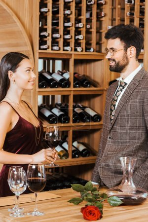 happy elegant couple chatting at wine storage