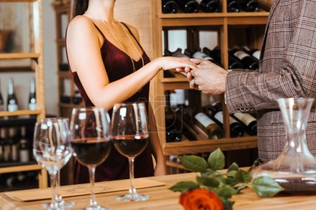 cropped shot of elegant couple having date at wine storage and holding hands