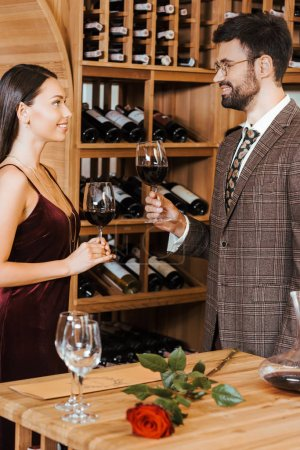 beautiful elegant couple toasting with wine glasses at wine storage