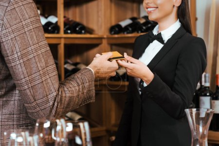 cropped shot of female wine steward taking credit card from customer at wine store