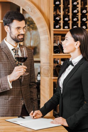 wine steward making notes while talking to client at wine store