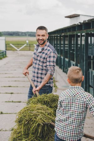 father and son in checkered shirts working together at farm