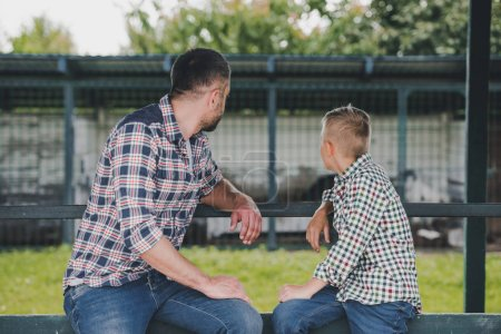 Photo for Side view of father and son in checkered shirts sitting together and looking away at ranch - Royalty Free Image