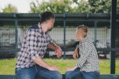 side view of father and son in checkered shirts sitting together and looking away at ranch