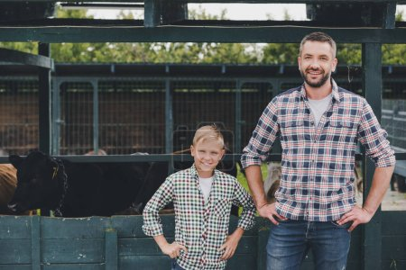 Photo for Happy father and son standing with hands on waist and smiling at camera on farm - Royalty Free Image