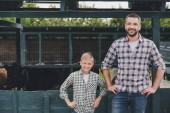happy father and son standing with hands on waist and smiling at camera on farm