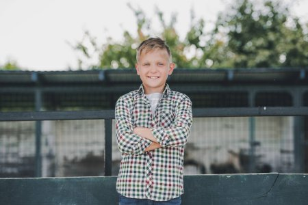 adorable child in checkered shirt standing with crossed arms and smiling at camera on farm