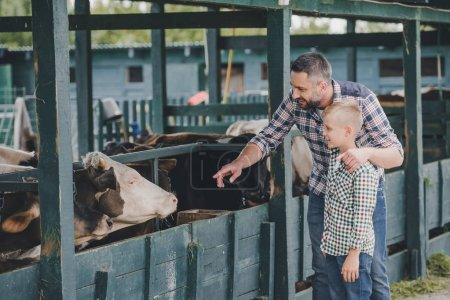 Photo for Happy father and son in checkered shirts looking at cows in stall - Royalty Free Image