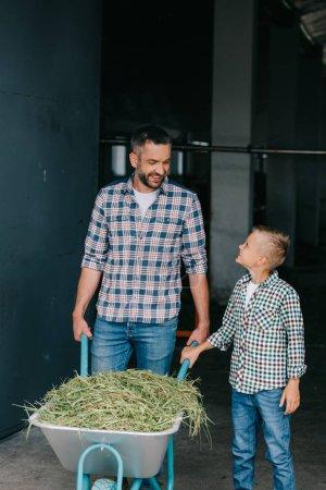 Foto de Feliz padre e hijo empujando la carretilla con la hierba y sonriendo uno al otro en puesto - Imagen libre de derechos