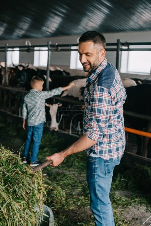 Photo for Happy father and son feeding cows in stall - Royalty Free Image