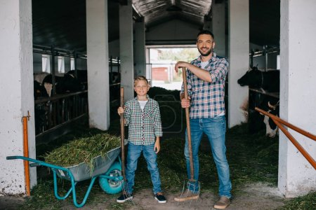 father and son holding pitchforks and smiling at camera while working together in stall