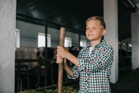 smiling boy holding rake and looking away while working at cowshed