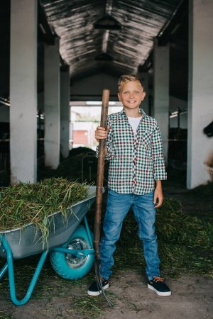 happy boy in checkered shirt standing with pitchfork and smiling at camera in stall
