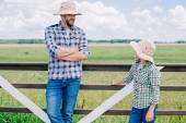 father and son in panama hats looking at each other while standing near fence at farm