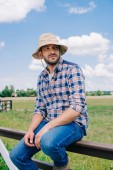 pensive middle aged farmer in panama hat sitting on fence and looking away at field