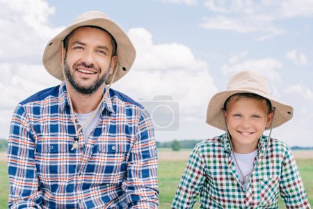 Photo for Happy father and son in checkered shirts and panama hats smiling at camera outdoors - Royalty Free Image