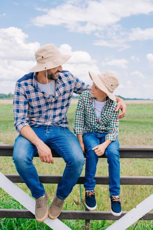 happy father and son in panama hats sitting on fence and smiling each other at farm