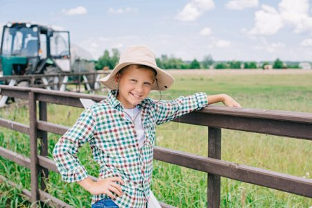 cheerful child in panama hat leaning at fence and smiling at camera on farm