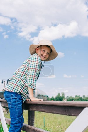 cheerful child in panama hat climbing on fence and smiling at camera on farm
