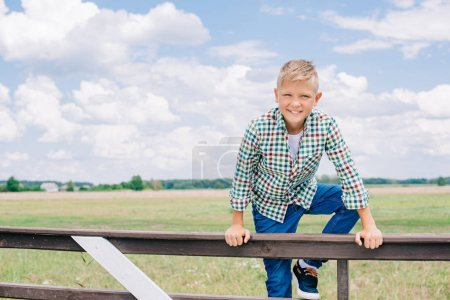 happy boy climbing on fence and smiling at camera on farm