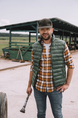 handsome middle aged farmer in cap smiling at camera while standing with hand on waist at ranch
