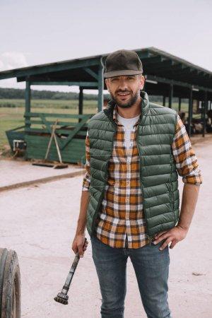 Photo pour Beau milieu agriculteur âgé de cap souriant à la caméra en se tenant debout avec les mains sur la taille au ranch - image libre de droit