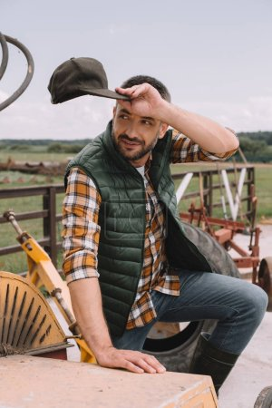 handsome male farmer holding cap and looking away while working at ranch