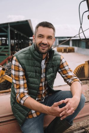 handsome male farmer sitting and smiling at camera at ranch