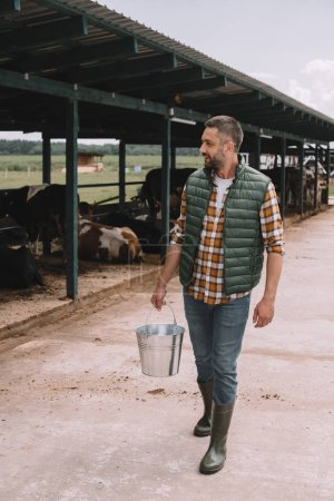 Photo for Handsome male farmer holding bucket and looking at cows in cowshed - Royalty Free Image