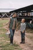 père avec seau et petit-fils en caoutchouc, bottes regardant les uns les autres tout en travaillant ensemble au ranch