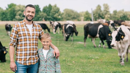 Photo for Happy father and son smiling at camera while standing near grazing cattle at farm - Royalty Free Image