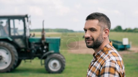 Photo for Side view of handsome middle aged farmer smiling while standing near tractor in field - Royalty Free Image