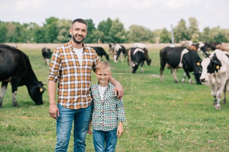 Photo for Father and son smiling at camera while standing near grazing cattle at farm - Royalty Free Image