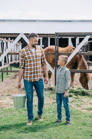 Foto de Padre con cubo y pequeño hijo sonriendo unos a otros mientras que se coloca cerca de caballo en el Rancho - Imagen libre de derechos