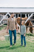 father with bucket and little son smiling each other while standing near horse at ranch
