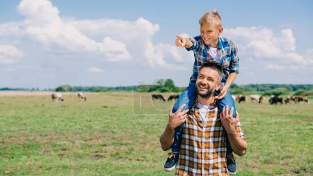 Photo for Happy father carrying smiling son on neck and looking away in field - Royalty Free Image