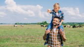 happy father carrying smiling son on neck and looking away in field