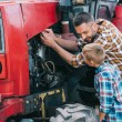 Happy father and son repairing tractor engine toge...