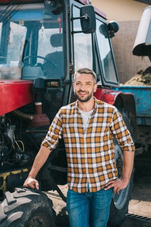 handsome middle aged farmer standing near tractor and smiling at camera