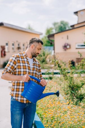 handsome middle aged farmer in checkered shirt watering flowers in garden