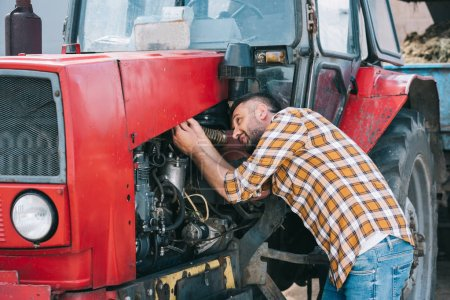 handsome middle aged farmer in checkered shirt repairing tractor