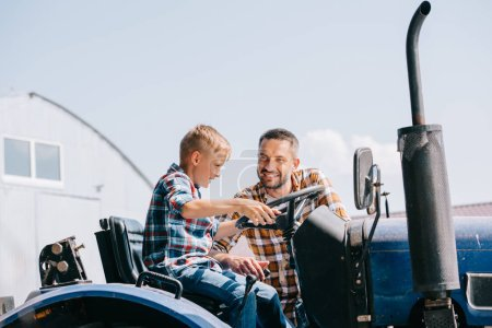 happy father looking at smiling son sitting in tractor on farm