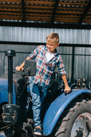 happy child sitting in tractor and looking away on farm