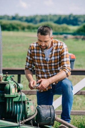 handsome middle aged farmer repairing tractor engine