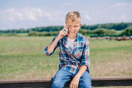 happy child talking by smartphone while sitting on fence and smiling at camera